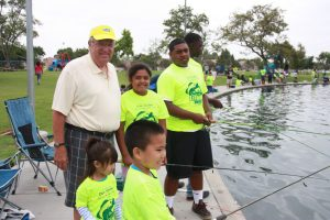 Don Knabe Los Angeles County Supervisor with children casting their fishing rods. From right to left Makoa B., Nalani B., Jazmine Lacey, and John Lacey Jr.
