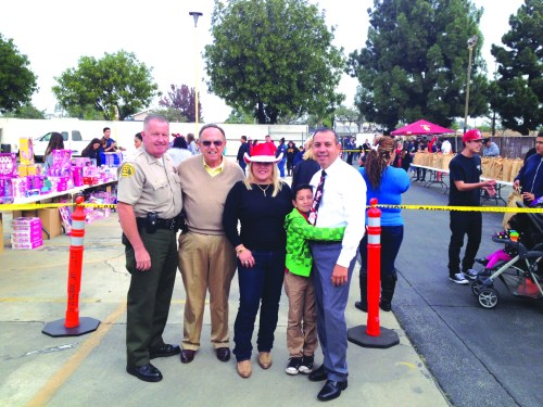HELPING OUT: From left to right: Norwalk Sheriff's Commander Pat Maxwell, Norwalk Councilman Luigi Vernola, founder of the Santa's Sleigh Foundation, former Pico Rivera Mayor Gracie Gallegos, and newly elected State Senator Tony Mendoza with his son Antonio, Jr. In the background is the donated toy station and the hundreds of bags of food for families in need. Photo by Brian Hews.