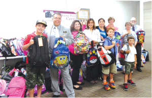 Kaiser Permanente representatives along with Mark Anthony-Ruiz (second from left) giving backpacks to ABCUSD students, Kaiser donated over 170 backpacks.