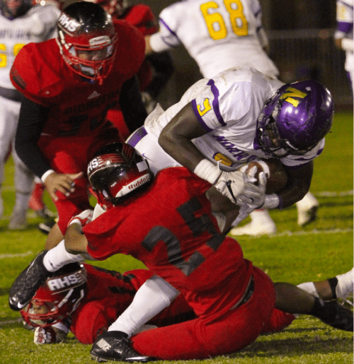 Photo caption: Artesia senior cornerback Andres Covarrubias makes a tackle on Norwalk senior running back Jordan Thomas in last Friday night's Suburban League game. Thomas led the Lancers with 125 yards and one rushing touchdown. Norwalk won 40-28 to clinch at least a share of third place.
