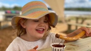 Photo of a young girl enjoying a fresh portion of churros and chocolate at The Wave in Bristol