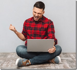 Portrait of a happy young man using laptop and celebrating success isolated over gray background