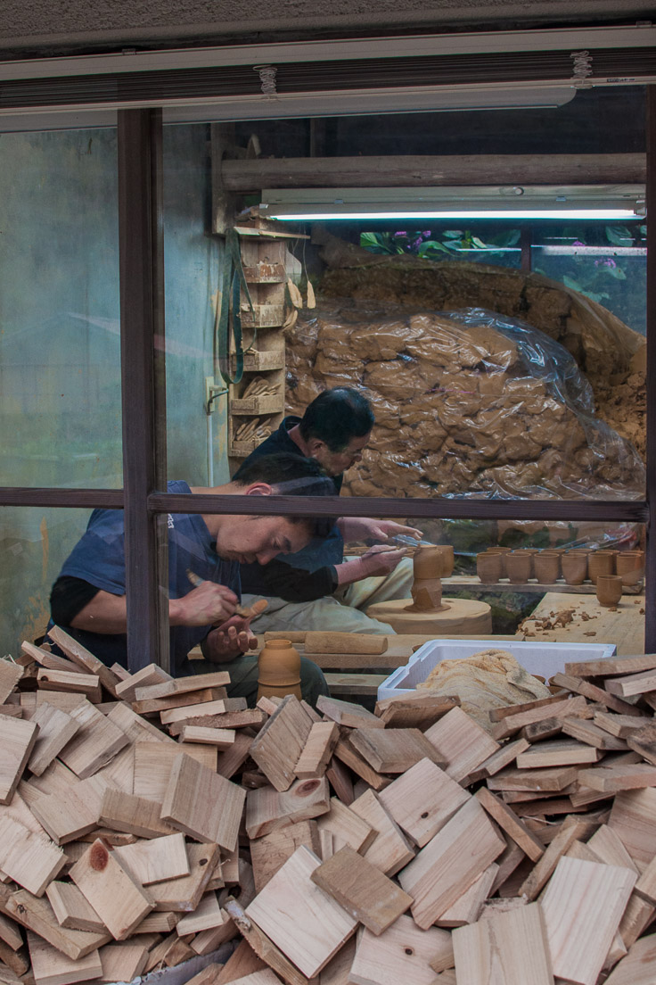 View of two potters through a window with a pile of clay behind them in Japan