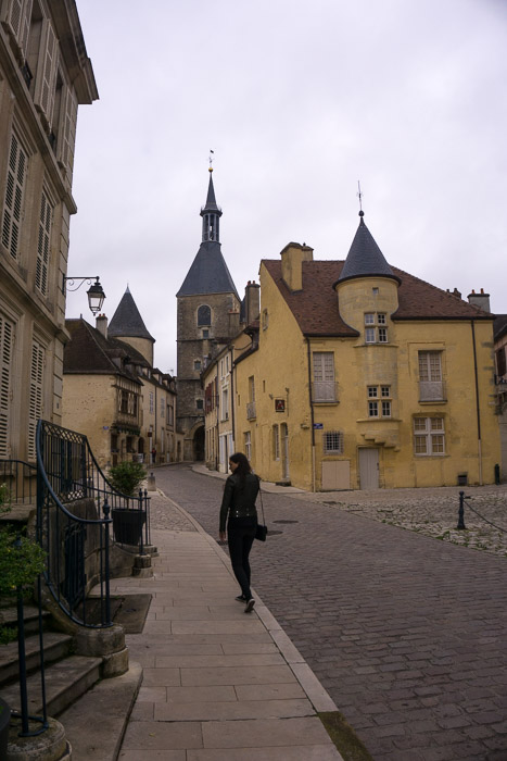 Girl walking through old buildings in Avallon France | Lost Not Found | French Road Trip