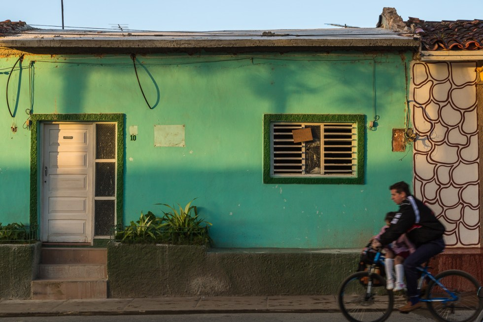 A man riding his bike with a child in front of a green building in Vinales Cuba | LOST NOT FOUND| Cuba | Vinales | Street Photography
