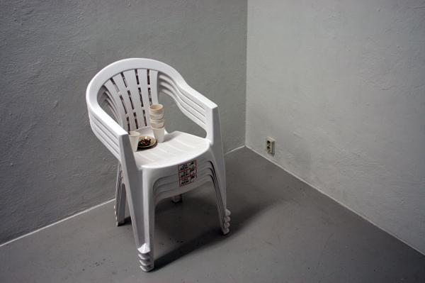 De vier stoelen met de koffie van de dag en de restjes sigaretten van de dag