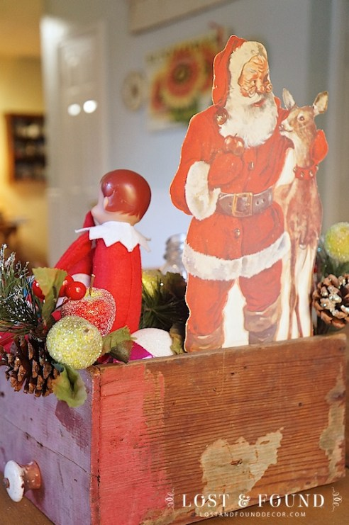 Gather together Christmas themed decor in primitive box for a fun display