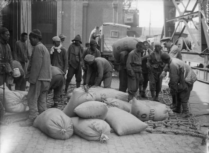 Men of the Chinese Labour Corps load sacks of oats onto a lorry at Boulogne while supervised by a British officer (12 August 1917) - wikipedia.org
