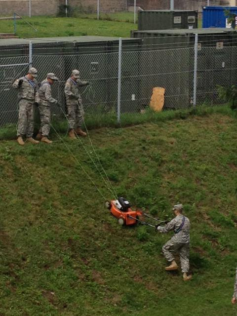 four soldiers operating a lawn mower