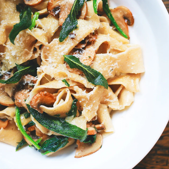 bowl of pasta with greens and mushrooms
