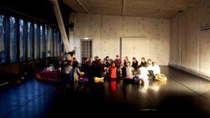 Living Archive Feminist Fiest. Bild på en grupp människor (ca 20 st) som sitter i en ring i ett rum med bara en ljuskälla. Foto: Elin Magnusson