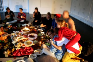 Människor sitter i en ring. I ringen står det bland annat mat, ljus och en picknickkorg. På en av personernas rygg har två barn klättrat upp. Foto: Elin Magnusson.