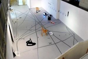 """Bild på ett vitt rum med grått golv. Golvet har mörkgråa streck och kryss. På golvet står två TV-apparater, tre trästolar och andra objekt. På väggen hänger många A4-ark med en person på. Det står också """"Dagens sanning/note of the day"""" på väggen."""