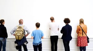 Guidad tur. Bild på sex personer som står med nästan mot en vit vägg. Vi ser deras ryggar. Foto: Björn Bengtsson