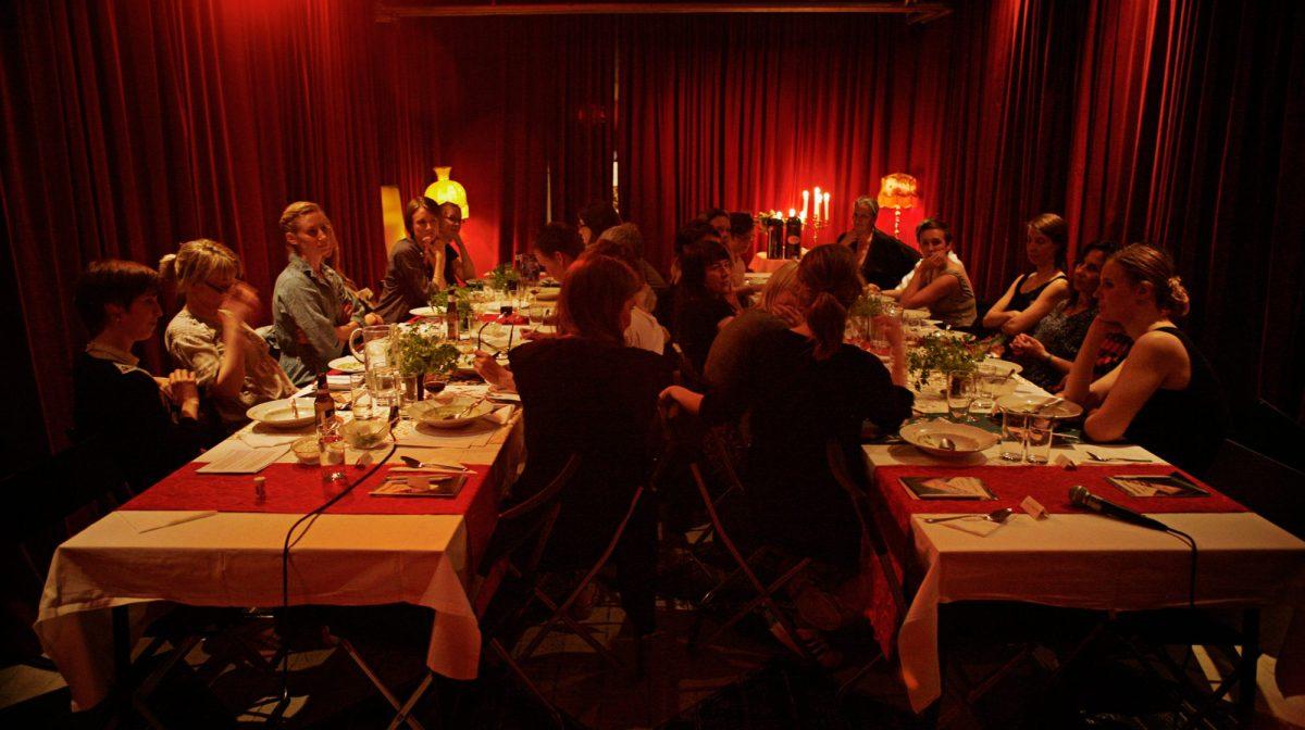 Judy Chicago: Bild på ca 20 personer som sitter vid två långbord med ett rött sammetsdraperi bakom. Foto: Eva Mag
