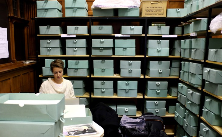 Louise gör research på Glasgow Women's Library, 2014. Louise sitter till vänster i bilden och har massor av grönblå kartonger bakom sig.