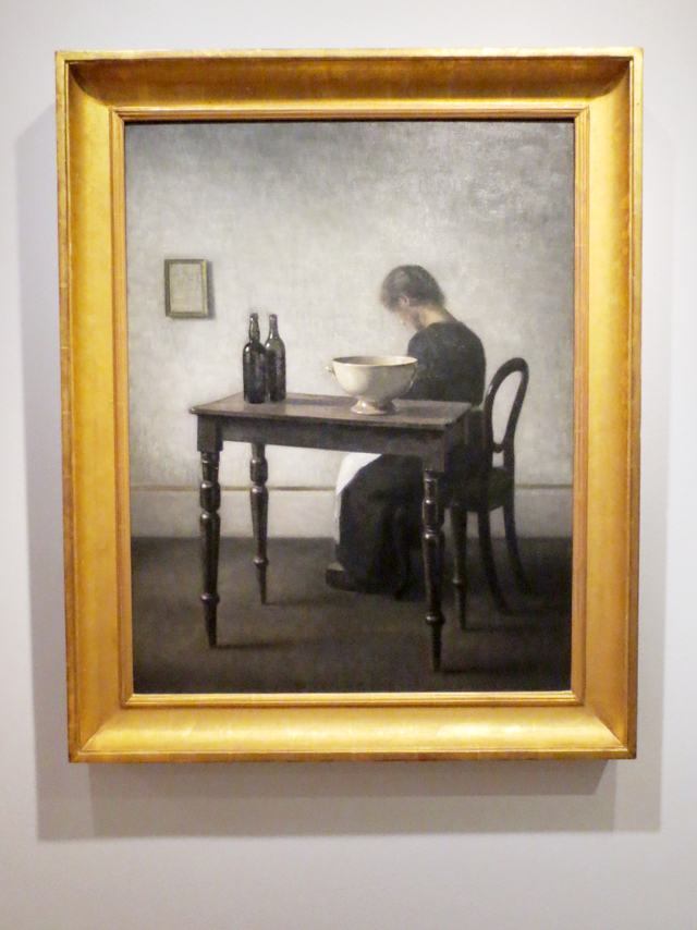 vilhelm-hammershoi-interior-with-woman-sitting-at-table-showing-at-ago-spring-twenty-sixteen