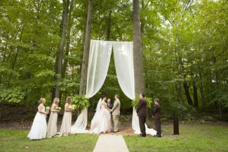 fabric alter hanging between two trees for outdoor ceremony