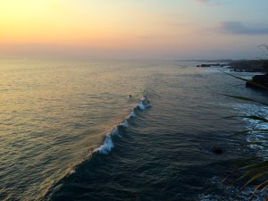 waves crashing at Tanah Lot temple surfers Bali indonesia sunset spot