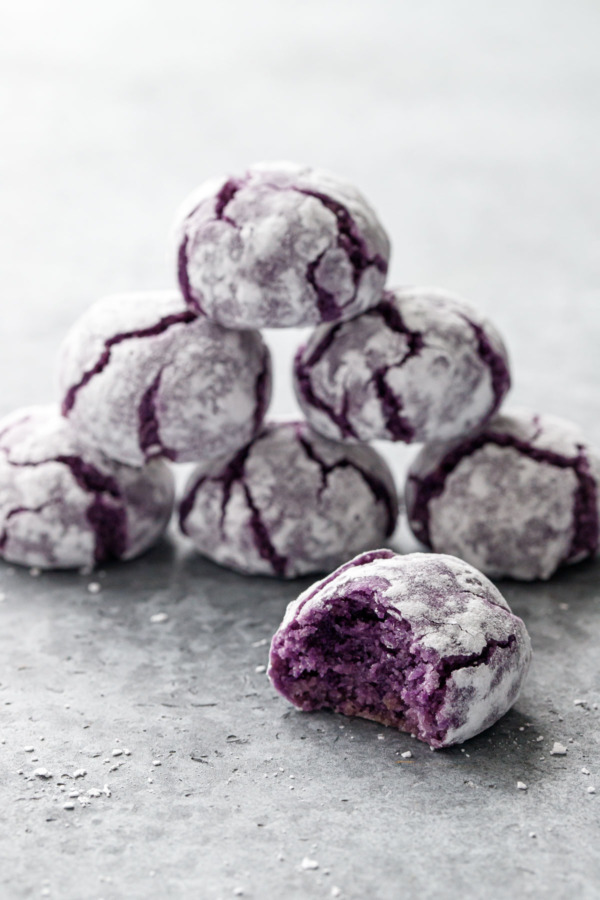 Stack of purple ube amaretti crinkle cookies on gray background, bite out of one cookie in the foreground