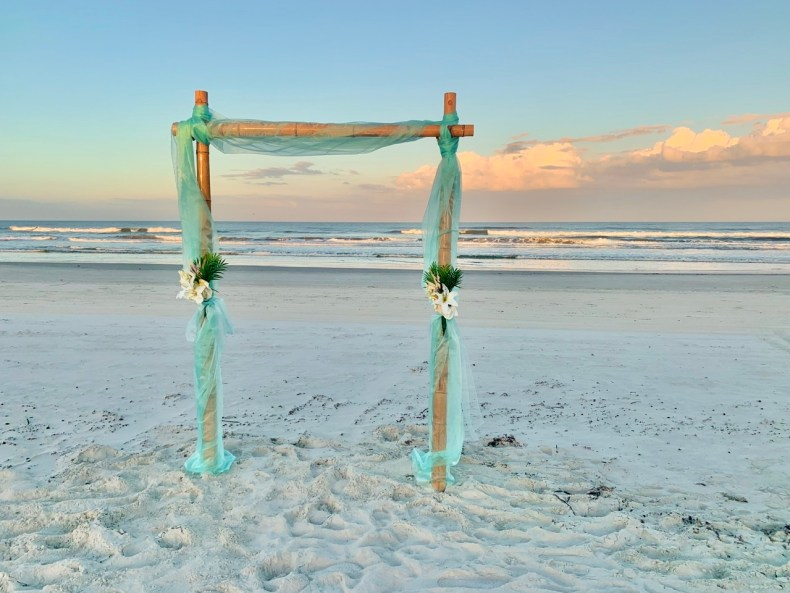 Photo of beach wedding arch made of bamboo at sunset