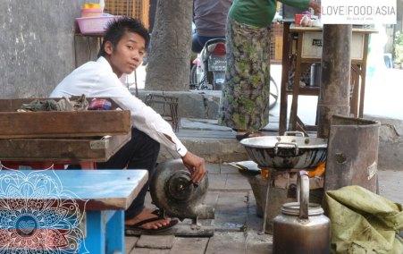 Ein Junge macht Tee in Mandalay