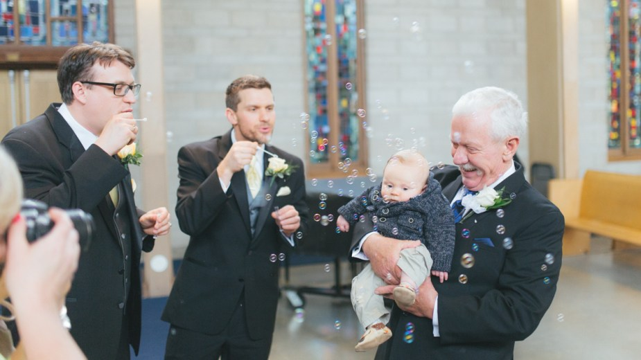 Father, baby and groomsmen having fun with bubbles after the ceremony