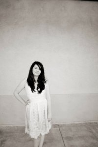 Megan N smiles as she stands in front of a blank wall. She is a Sacramento therapist that offers treatment for anxiety in Sacramento, CA, grief counseling, and others services.