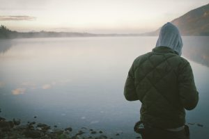 A person in a hoodie overlooks a vast lake alone. This could represent the isolation of grief. Contact an online grief counselor in Sacramento, CA for more info on grief counseling in Sacramento, CA.