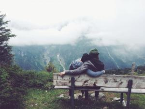 A couple embrace while sitting on a bench overlooking mountains. This could represent how online couples sex therapy in Sacramento, CA can support a relationship. Learn more about online couples therapy and marriage counseling in California today.