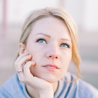 A woman looks off with a thoughtful look while resting her head on her hand. She appears to be lost in thought. This could symbolize someone thinking about the many questions that come from starting anxiety treatment. Contact an anxiety therapist for answers to any questions you may have, and learn how treatment for anxiety can support you.