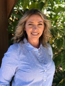 Nadia smiles at the camera in front of lush foliage. She is a Sacramento therapist that offers online therapy in california. Contact an online therapist for support with anxiety treatment, online couples therapy and marriage counseling in California, and other services.