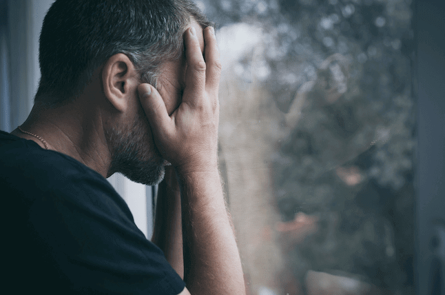 A man covers his face with his hands as he stands next to a window. He appears upset about something on his mind. This could symbolize the conflict that anxiety can create. An anxiety therapist in Sacramento, CA can support you with online anxiety therapy to overcome stress. Contact us today to begin anxiety treatment.