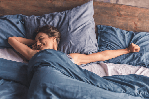 A smiling woman stretches in bed. A sex therapist can offer support with online sex therapy. Contact a sex therapist for info on sex therapy in Sacramento, CA today!