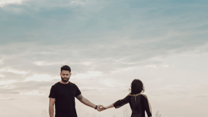 A distant couple let their hands drift apart as they walk away. Contact an online therapist for relationship support. Wee offer online couples therapy and marriage counseling and other services.