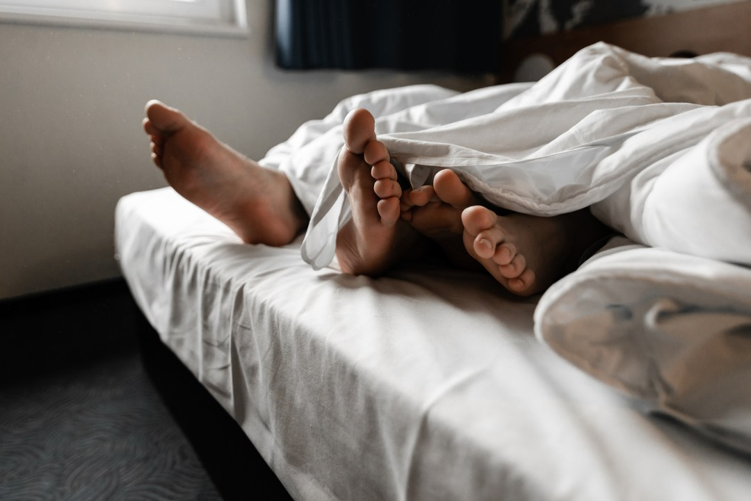 Two sets of feet can be seen peaking out from the end of a bed. This could symbolize a couple enjoying renewed intimacy as a result of online sex therapy in Sacramento, CA. Contact an online sex therapist for support. Online sex therapy can provide support for you today.