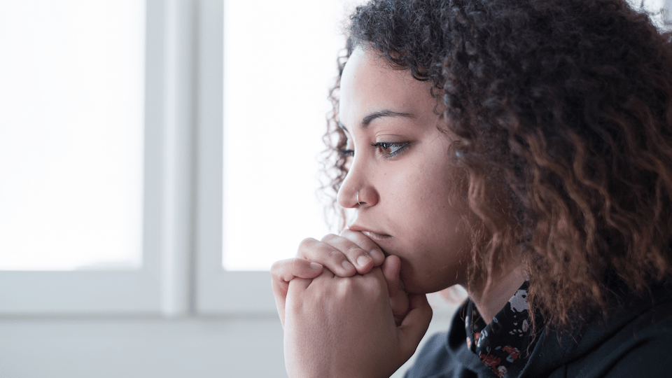 Sad woman sits with her hands by her face after suffering a loss. She gets grief counseling in Sacramento, CA at Love Heal Grow 95816