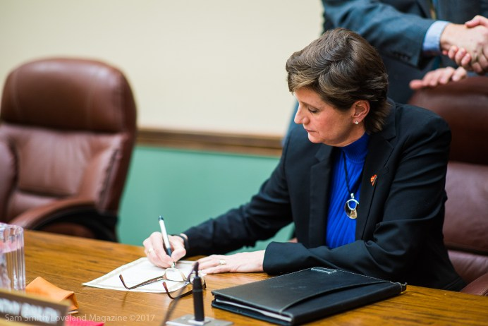 Bailey signs a document in order to secure her position as mayor of Loveland