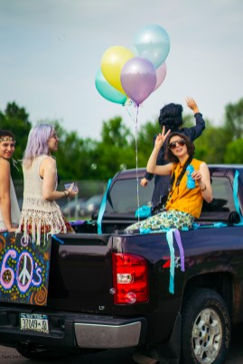 Olivia Buell, Lucy Johnson, Abby Wright and Isabella Huelsman ride a 60's themed float