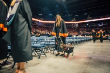 Abie Baker and her dog walk to their seat