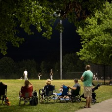 Parents sit along the outfield to watch their kids play during this Wednesday night pick-up game.