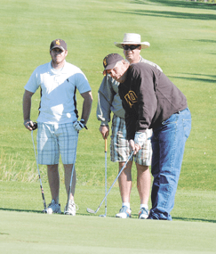 Brian Green chips onto the third hole green during the North Big Horn Hospital Friends of the Foundation Tournament Saturday at Foster Gulch as Jake (left) and Jay Bischoff look on. David Peck photos