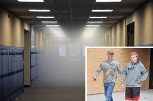 """School officials quickly cleared Lovell Middle School Monday morning when smoke filled the hallway as part of a drill initiated by the school and the Lovell Volunteer Fire Dept. At the right, LVFD Capt. Bob Mangus escorts student Quinn Lindsay from the building, one of three students who purposely """"hid"""" in the school as part of the drill. David Peck photos"""
