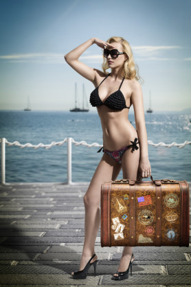 sexy woman tourist with bikini taking old fashion suitcase in the hand and searching something with her look on a pier