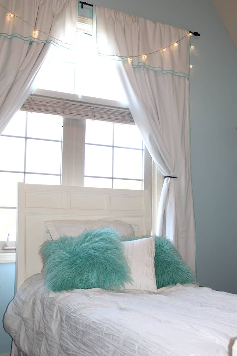 Tween girl bedroom makeover with before and after pictures, IKEA string lights, white bedding with blue accent pillows