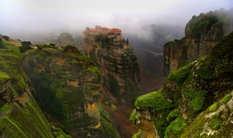 """The caves in Meteora, Greece, had inhabitants for fifty millennia, but due to raids, """"hermit monks"""" moved to the safety of sandstone rock pinnacles in the 9th century and began building monasteries. More monks and nuns came, building more monasteries perched high upon the cliffs."""