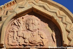 Carving of God with almond-shped eyes holding a head of John the Baptist, Noravank, Armenia