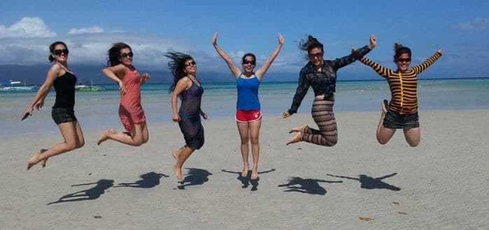 Girls doing a jump shot photo on the beach of Cagbalete Island.