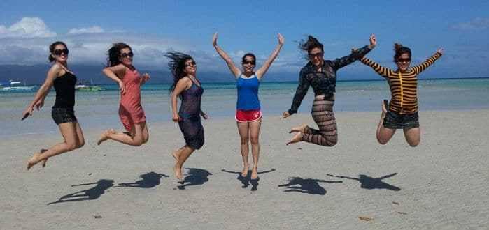 Girls doing a jump shot photo on the beach of Cagbalete Island.