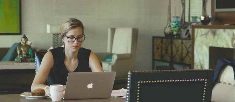 Woman working from home on a lap top to earn extra money